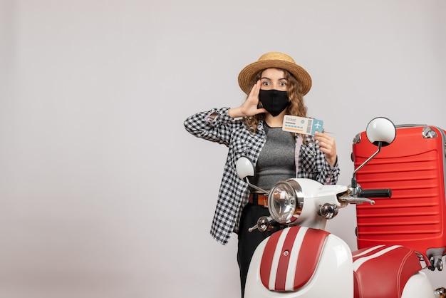 Verrast mooie vrouw met kaartje staande in de buurt van bromfiets rode koffer