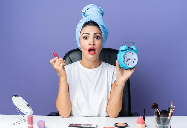 Verrast mooie vrouw zit aan tafel met make-up tools gewikkeld haar in handdoek met lippenstift met spiegel
