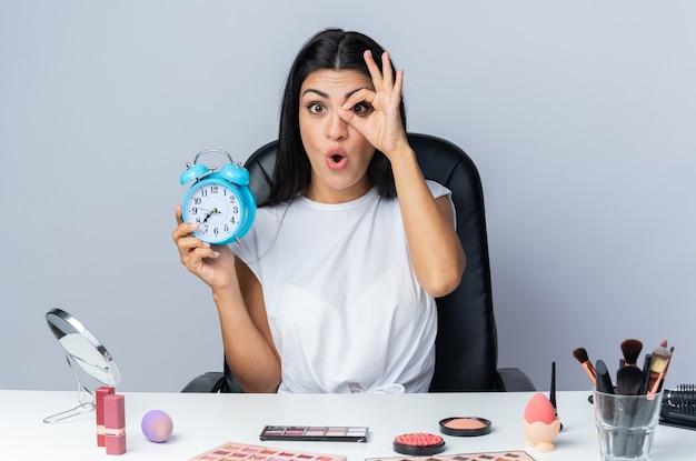 Verrast mooie vrouw zit aan tafel met make-up tools met wekker met blik gebaar