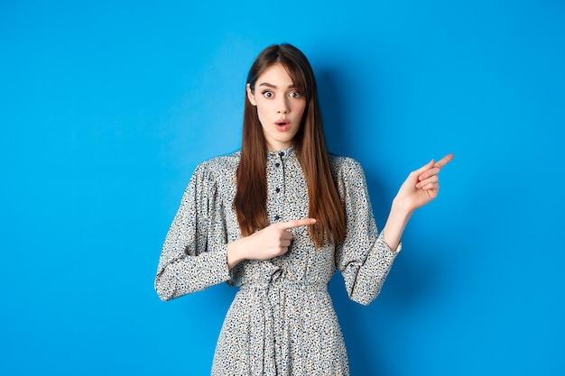 Verrast natuurlijk meisje in jurk zegt wow wijzende vingers naar promo en ziet er onder de indruk uit v...