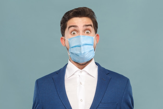 Verrast of geschokt jonge man met chirurgisch medisch masker kijken naar camera met grote ogen