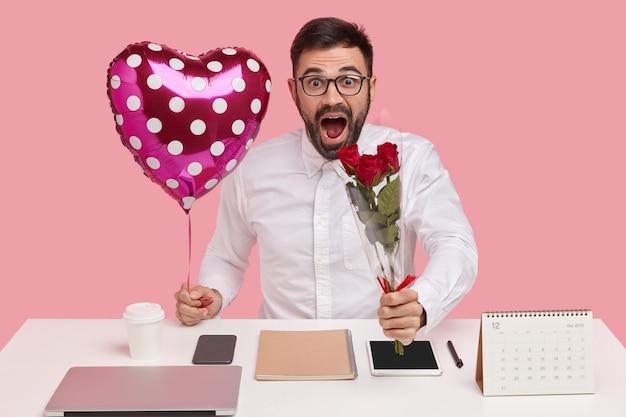 Verrast ongeschoren jong mannetje draagt boeket en ballon in de vorm van valentijn, geschokt om compliment te horen