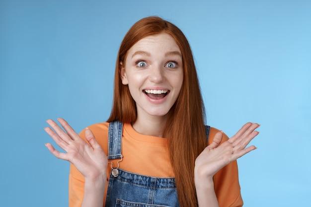 Verrast opgetogen gelukkig vriendelijk ogende geamuseerde roodharige vriendin leert ongelooflijk goed nieuws feliciteren vriendin gefascineerd brede ogen camera vreugdevol handen klappen verbaasd, blauwe achtergrond.