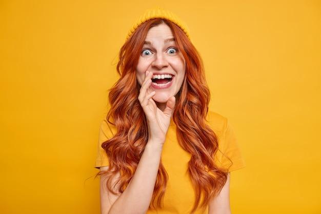 Verrast opgewonden roodharige europese vrouw met sproeten kijkt met ongeloof en geluk glimlacht in het algemeen voelt zich erg blij dat ze vrijetijdskleding draagt