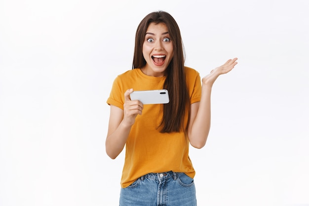 Verrast, opgewonden schattig meisje dat smartphone horizontaal houdt, één hand verbaasd opsteekt, blij glimlacht en kijkt naar de camera die vertelt dat ze het spelniveau heeft gewonnen, triomfeert en zich verheugt, witte achtergrond