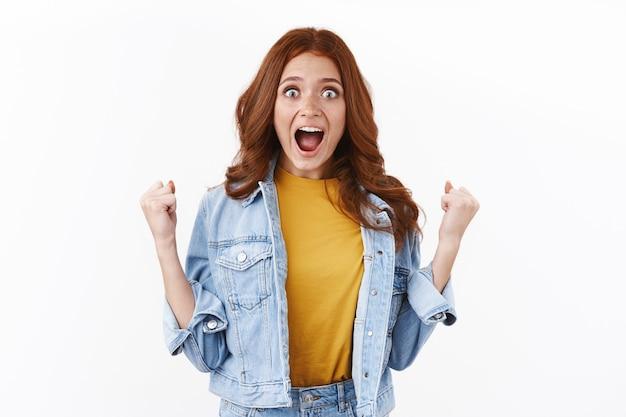 Verrast opgewonden schattige roodharige vrouw die loterij wint, vuistpomp staren camera verbaasd, schreeuw hoera, ja als triomf, succes behalen, geweldig nieuws vieren, witte muur