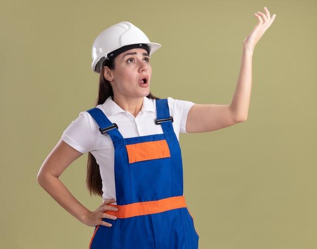 Verrast opzoeken jonge bouwersvrouw in uniforme punten met hand omhoog geïsoleerd op olijfgroene muur