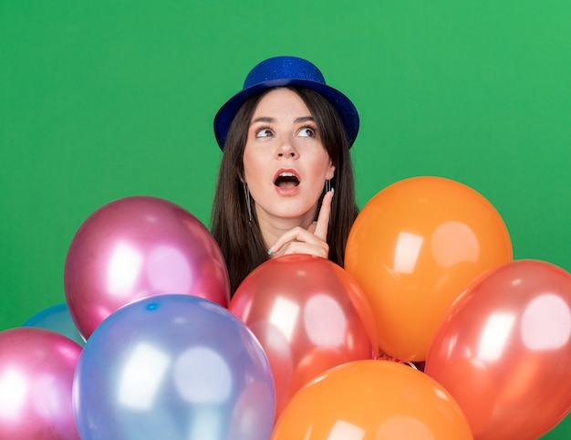 Verrast opzoeken van een jong mooi meisje met een feesthoed die achter de ballonnen staat en naar boven wijst