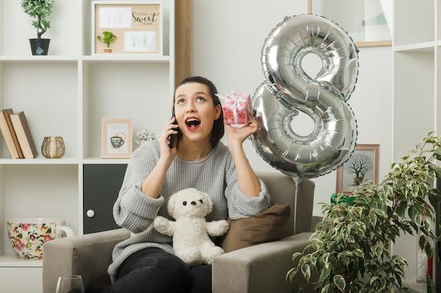 Verrast opzoeken van mooie vrouw op gelukkige vrouwendag die aanwezig is, spreekt op telefoon zittend op een fauteuil in de woonkamer