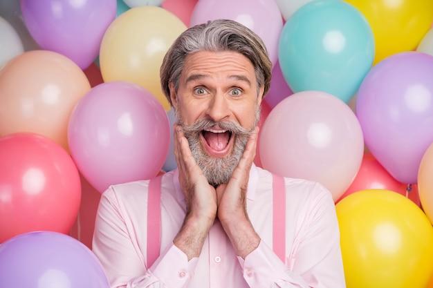 Verrast oude man raakt zijn gezicht met handen schreeuwen op lucht ballonnen achtergrond