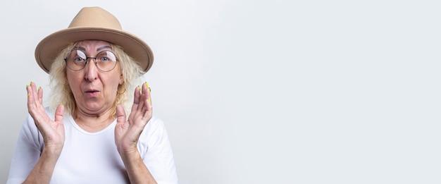Verrast oude vrouw in een hoed op een lichte achtergrond. banier.