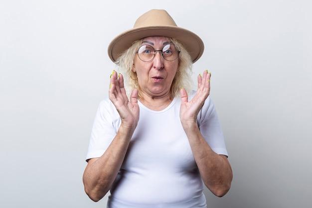 Verrast oude vrouw in een hoed op een lichte achtergrond.