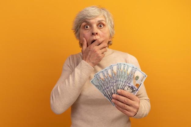 Verrast oude vrouw met een romige coltrui die geld vasthoudt en er recht uitziet terwijl ze de hand op de mond houdt