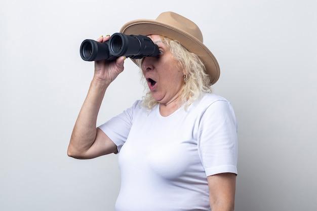 Verrast oude vrouw met verrekijker op een lichte achtergrond.