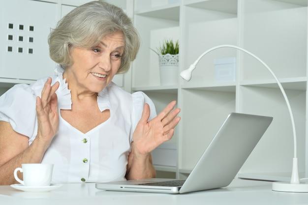 Verrast oudere vrouw die op laptop op kantoor werkt