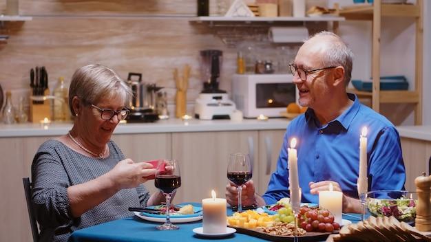 Verrast oudere vrouw met charmante glimlach zittend aan de tafel in de keuken die een kleine geschenkdoos opent vrolijk stel dat samen thuis eet, geniet van de maaltijd, hun jubileum viert