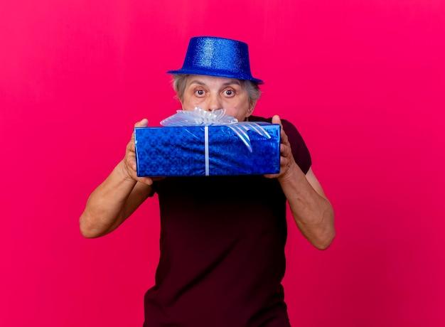 Verrast oudere vrouw met feestmuts houdt en kijkt naar camera over geschenkdoos op roze