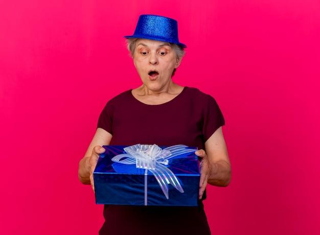 Verrast oudere vrouw met feestmuts houdt en kijkt naar geschenkdoos op roze
