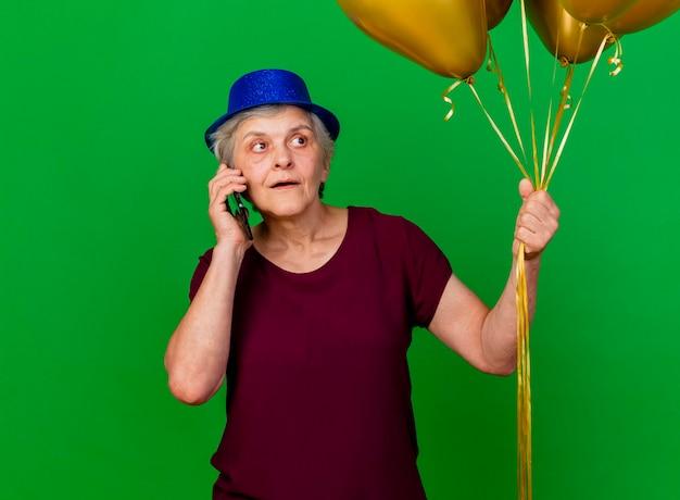 Verrast oudere vrouw met feestmuts houdt helium ballonnen en praat over telefoon kant op groen kijken