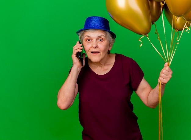 Verrast oudere vrouw met feestmuts houdt helium ballonnen praten over de telefoon op groen