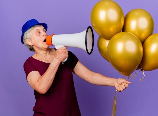 Verrast oudere vrouw met feestmuts houdt helium ballonnen vast en spreekt in luidspreker
