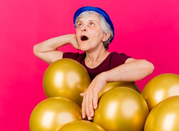 Verrast oudere vrouw met feestmuts legt hand op hoofd achter staan met helium ballonnen