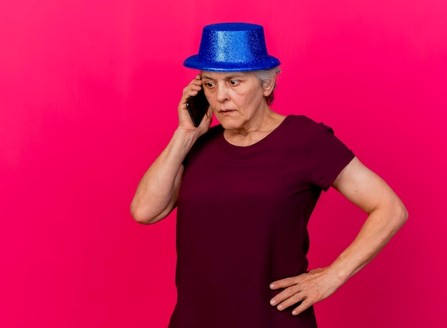 Verrast oudere vrouw met feestmuts legt hand op taille praten over de telefoon op roze