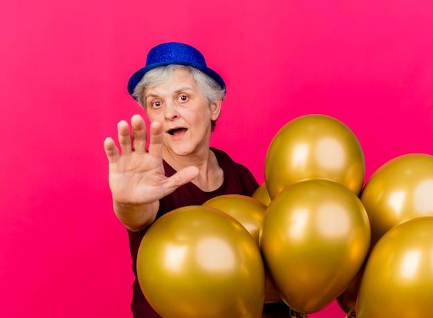 Verrast oudere vrouw met feestmuts permanent met helium ballonnen hand strekken op roze