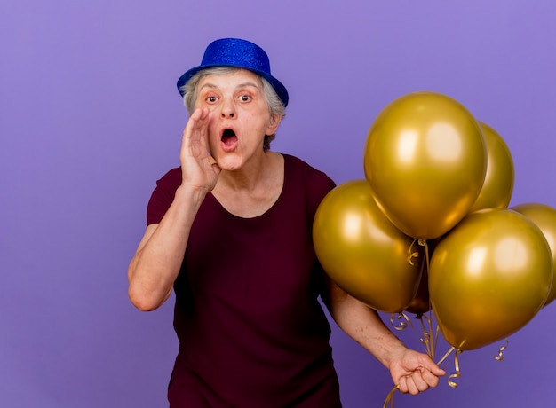 Verrast oudere vrouw met feestmuts staat met helium ballonnen die hand dicht bij mond geïsoleerd op paarse muur met kopie ruimte