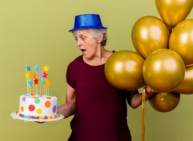 Verrast oudere vrouw met feestmuts staat met helium ballonnen kijken naar verjaardagstaart op olijfgroen