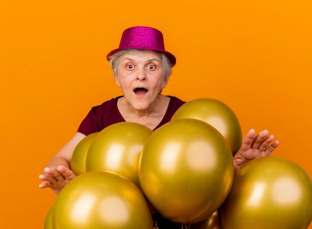Verrast oudere vrouw met feestmuts staat met helium ballonnen kijken naar voorzijde geïsoleerd op oranje muur