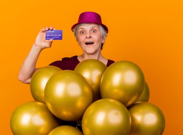 Verrast oudere vrouw met feestmuts staat met helium ballonnen met creditcard geïsoleerd op oranje muur