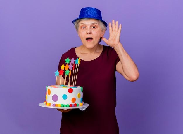 Verrast oudere vrouw met feestmuts staat met opgeheven hand met verjaardagstaart geïsoleerd op paarse muur met kopie ruimte