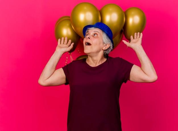 Verrast oudere vrouw met feestmuts staat voor helium ballonnen met opgeheven handen opzoeken op roze