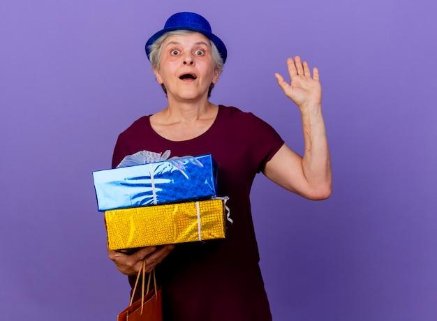 Verrast oudere vrouw met feestmuts steekt hand op en houdt geschenkdoos geïsoleerd op paarse muur met kopie ruimte