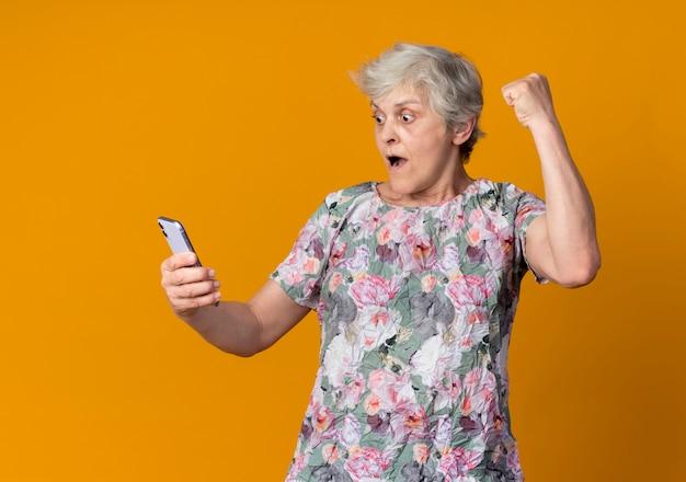 Verrast oudere vrouw steekt vuist omhoog kijken naar telefoon geïsoleerd op oranje muur