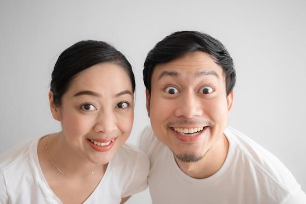 Verrast over paar grappig gezicht in wit t-shirt en een witte achtergrond.