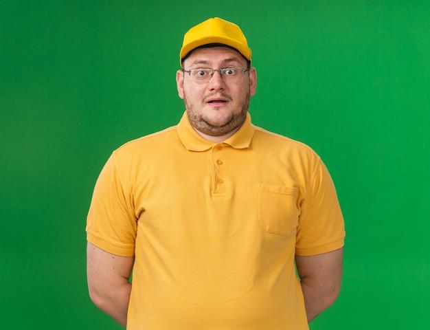 Verrast overgewicht jonge bezorger in optische bril geïsoleerd op groene muur met kopie ruimte