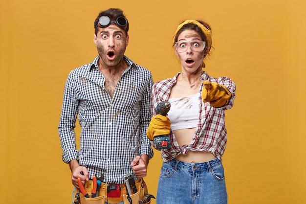 Verrast paar mannelijke en vrouwelijke elektrotechnici in veiligheidsbril en overall met verbaasde blikken, meisje met boor wijzende wijsvinger, iets schokkends tonen