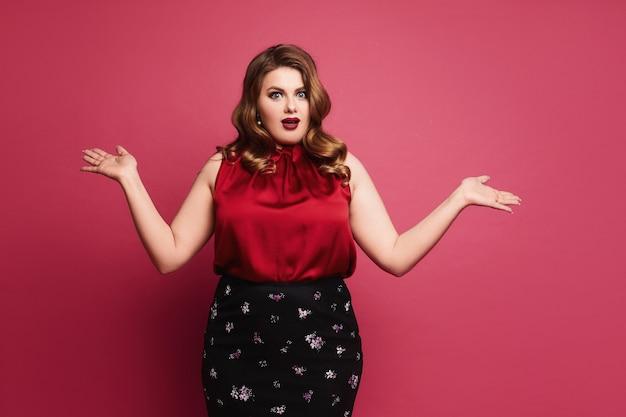 Verrast plus size model met lichte make-up in rode satijnen blouse en zwarte rok