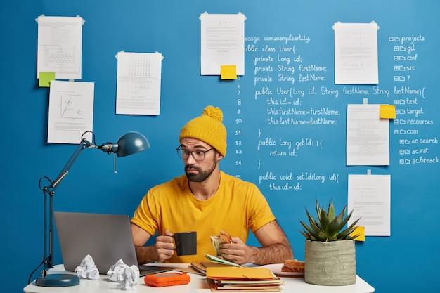 Verrast professionele mannelijke it-professionele freelancer gericht in de monitor van de laptop, probeert de code van de toepassing te verbeteren, koffie drinkt en sandwich eet.