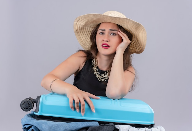 Verrast reiziger jong meisje, gekleed in zwart onderhemd in hoed die open koffer op witte achtergrond houdt