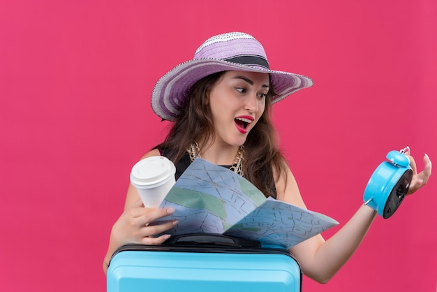 Verrast reiziger jong meisje, gekleed in zwart onderhemd in hoed met wekker en kaart op rode achtergrond