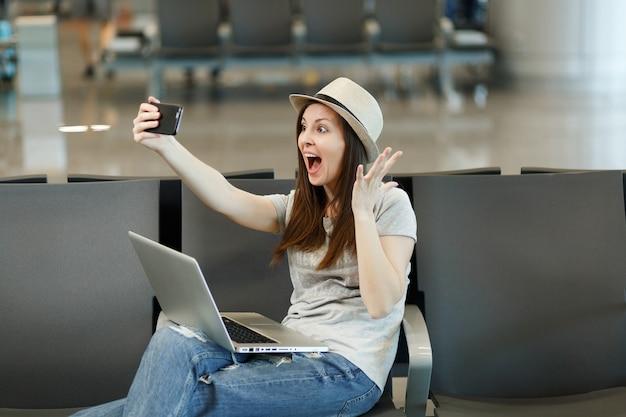 Verrast reizigerstoeristenvrouw die aan laptop werkt, selfie op mobiele telefoon doet, handen spreidt, wacht in lobbyhal op luchthaven