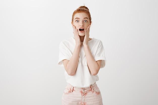 Verrast roodharig meisje staren verbaasd en zegt wow