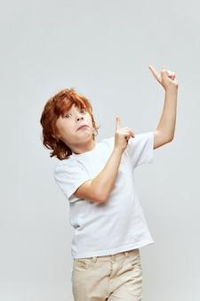 Verrast roodharige jongen gebaren met zijn handen geïsoleerd