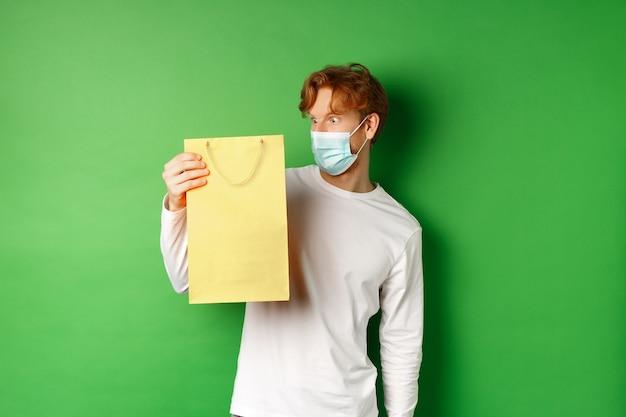 Verrast roodharige man die een cadeautje ontvangt, kijkend naar boodschappentas met nieuwsgierig gezicht, staande over groene achtergrond in gezichtsmasker van covid-19