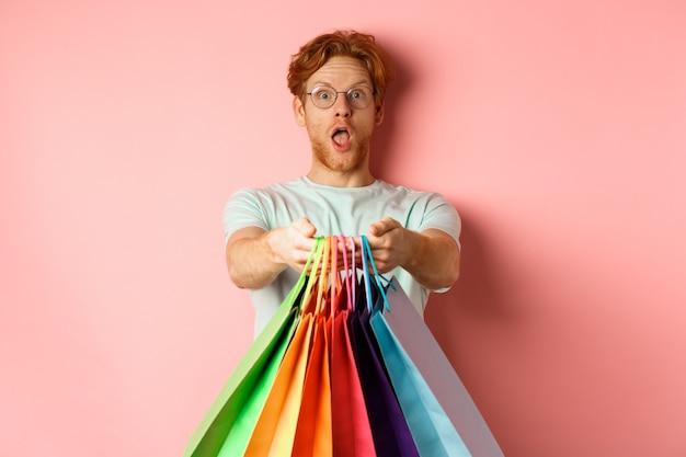 Verrast roodharige man strekt zijn handen uit met boodschappentassen, geef je geschenken, staande op roze achtergrond.