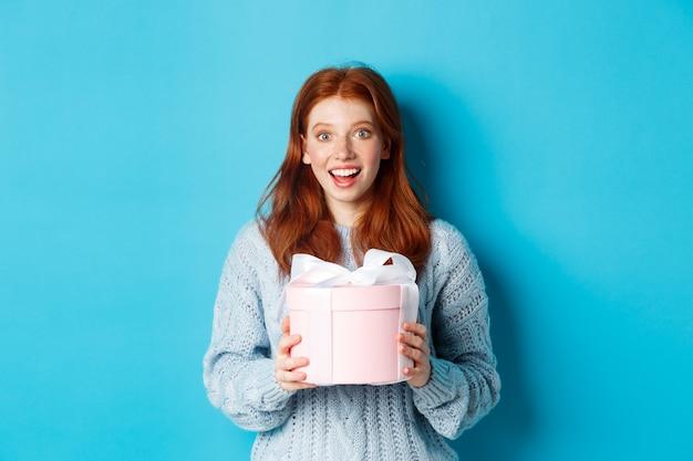 Verrast roodharige meisje dat valentijnscadeau ontvangt, doos met cadeau vasthoudt en verbaasd naar de camera staart, trui draagt, staande over blauwe achtergrond.