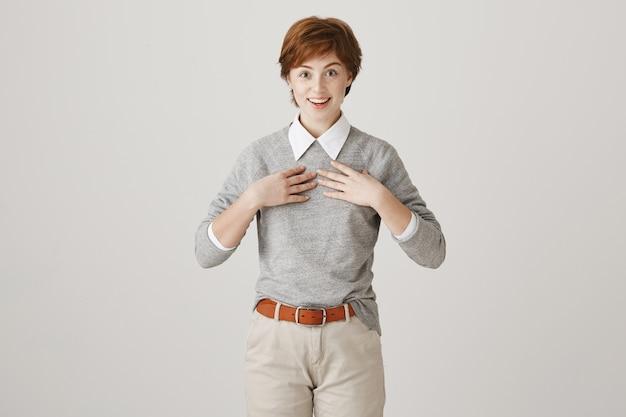 Verrast roodharige meisje met kort kapsel poseren tegen de witte muur